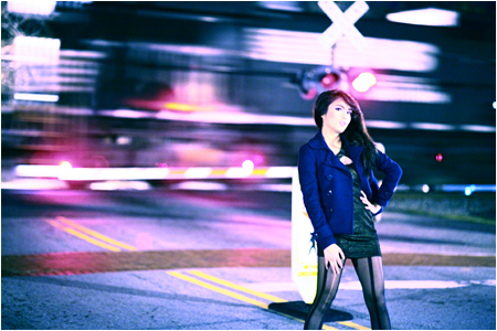 Model Standing in Front of a Passing Train at Night
