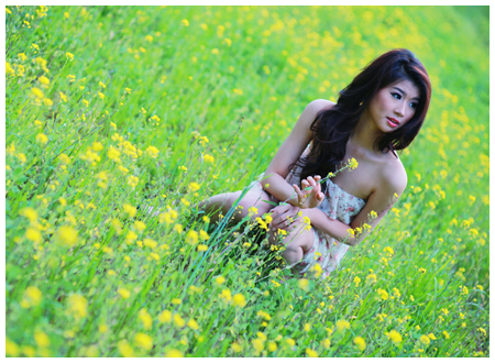 Young Woman sitting in a field of flowers