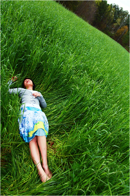 Photo of a Young Woman Lying in a Green Field of Rice