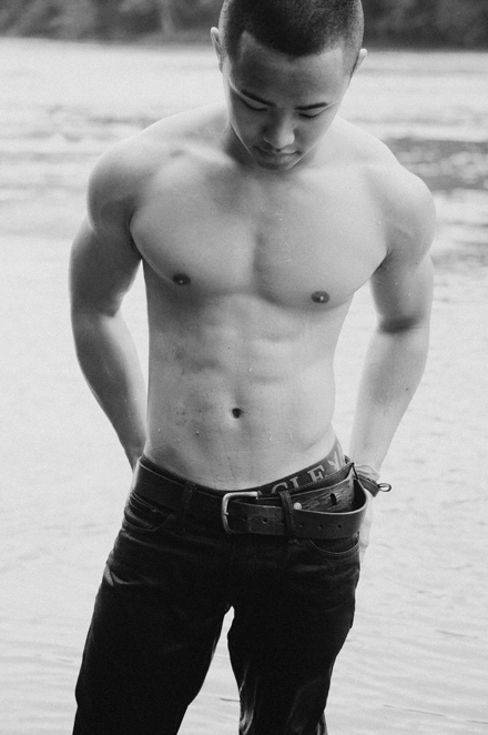 Black and White Photo of a Muscular Young Man posing in a River